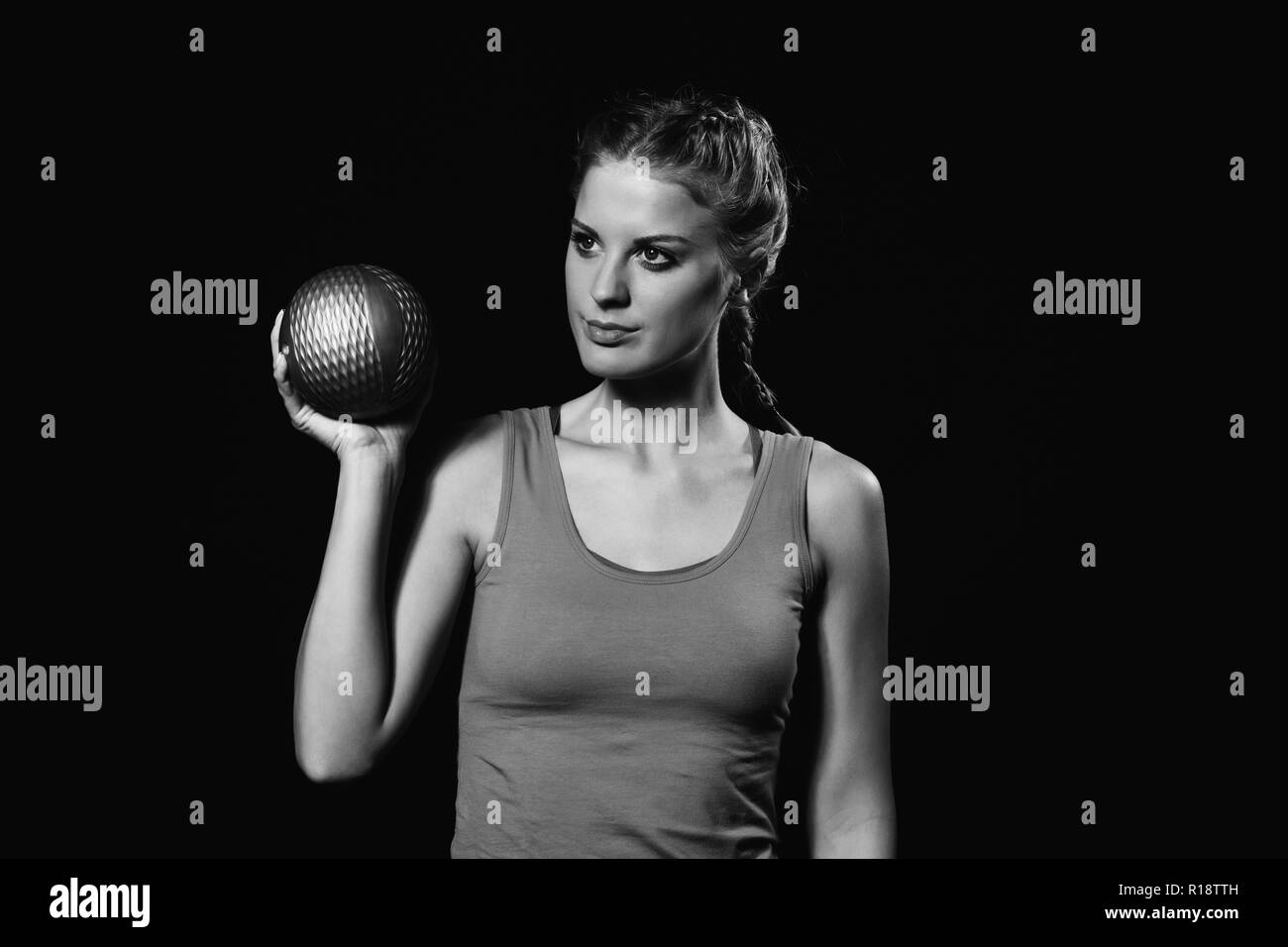 Beautiful young woman is exercising with medicine ball. Stock Photo