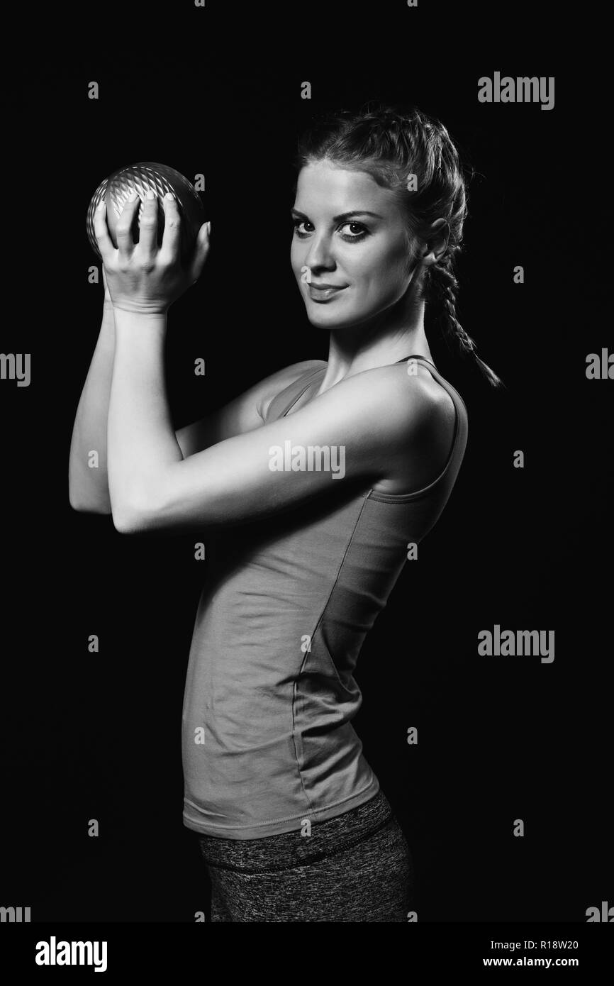 Beautiful young woman is exercising with medicine ball. - Stock Image