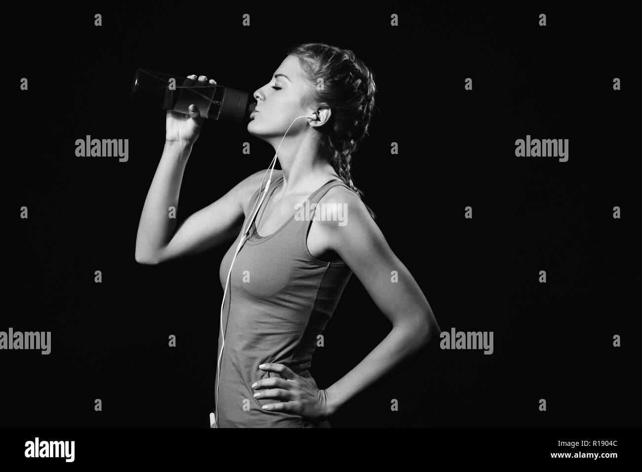 Beautiful woman is drinking water after exercise and listening music. Stock Photo