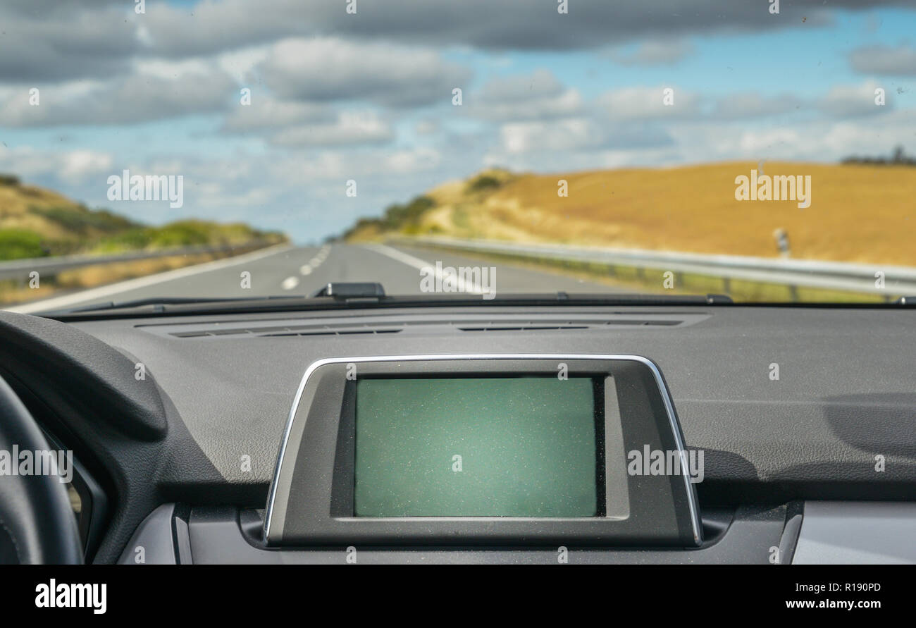 Selective focus of generic built in GPS navigator on dashboard of a car going down the scenic highway - Stock Image