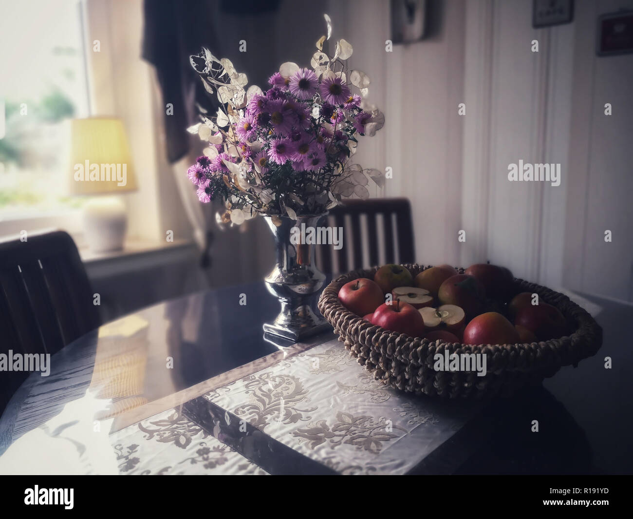 Autumnally decorate with asters, silver leaf (Lunaria) and an old variety of apples. Dark furniture and striped wallpaper in retro look. Flowers and f - Stock Image
