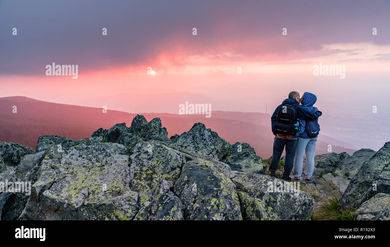 European romantic weekend getaway - a couple kissing on a mountain top under the setting sun - Stock Image
