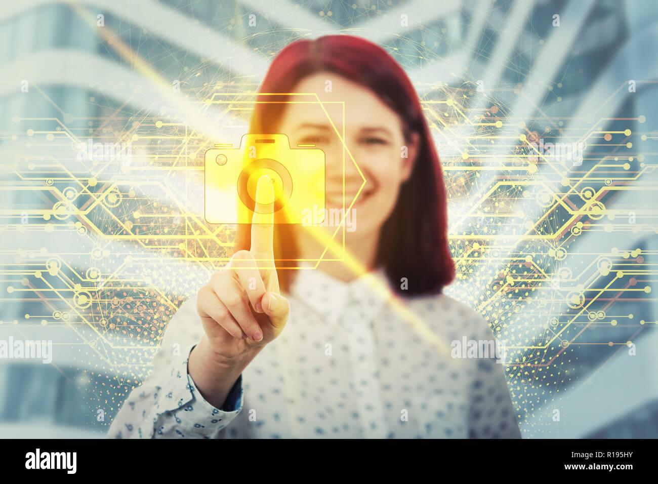 Smiling woman touching digital screen interface. Press on the golden camera icon. Modern technology in professional photography concept. Virtual busin - Stock Image
