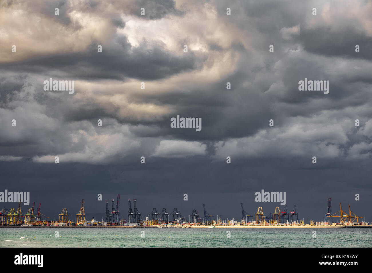 Very dark clouds over commercial dock - Stock Image