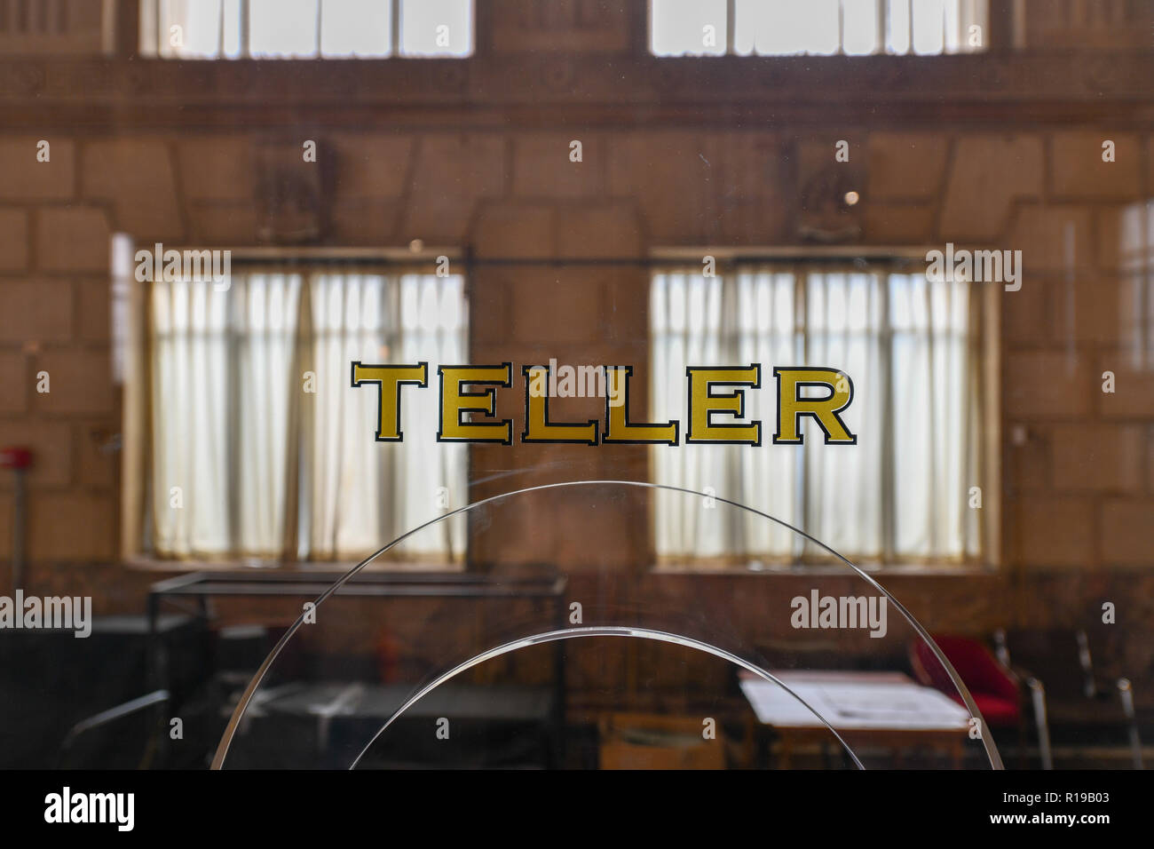 Old fashioned bank teller window sign in a classically styled building. - Stock Image