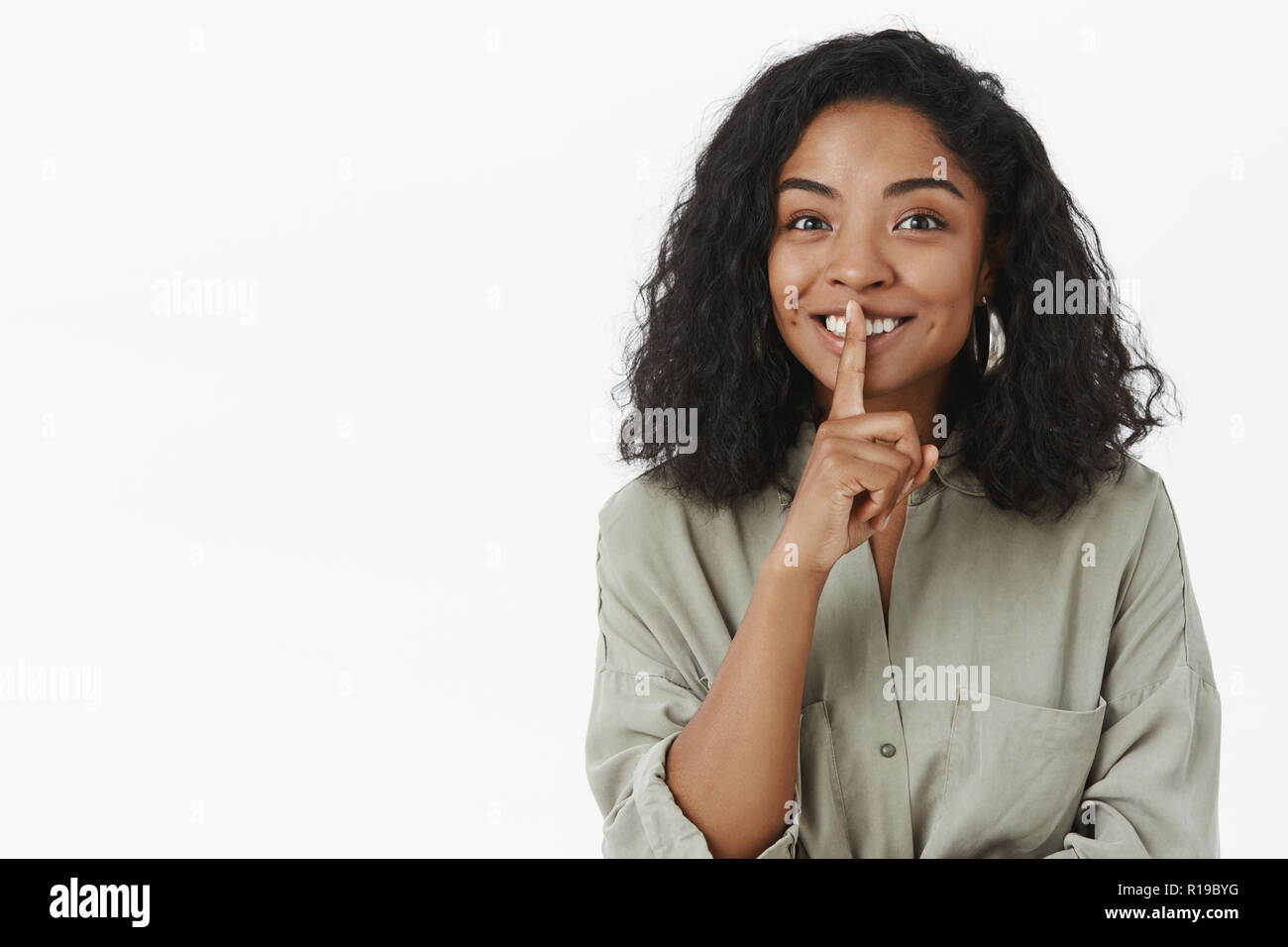 Shh can you keep secrets. Portrait of charming friendly-looking delighted  cute dark-skinned woman with curly hairstyle saying shush and smiling  prepar Stock Photo - Alamy