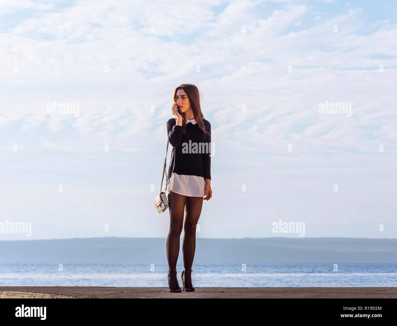 Standing teen girl outside full length Black tights - Stock Image