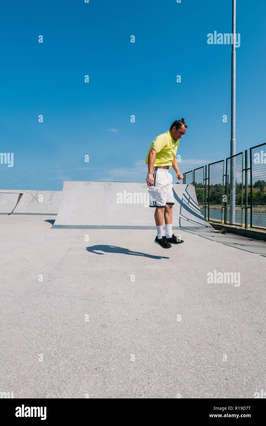Man doing parkour exercise outdoor in the skatepark - Stock Image