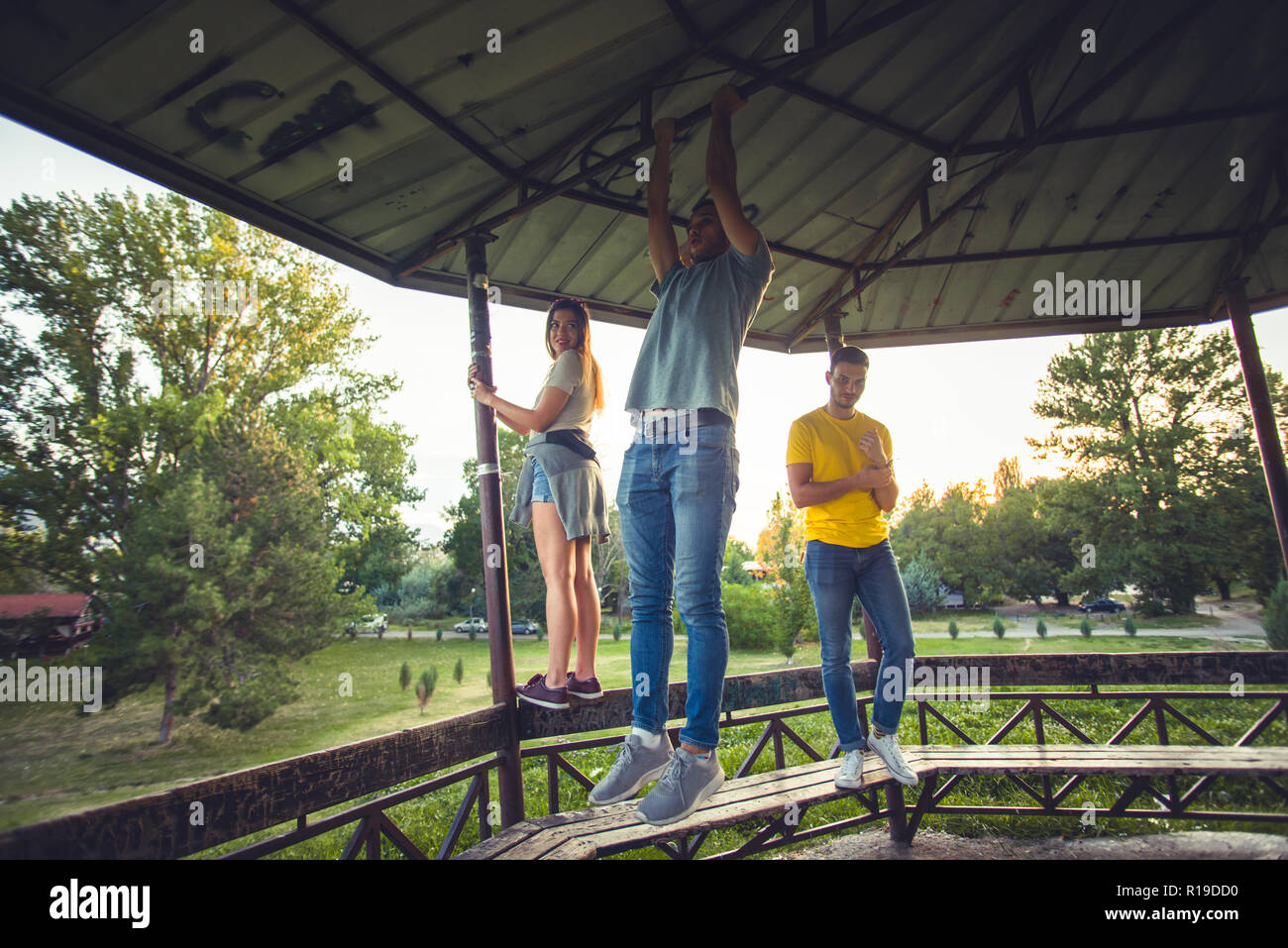 Young, careless people standing and climbing on wooden boards, having fun together - Stock Image