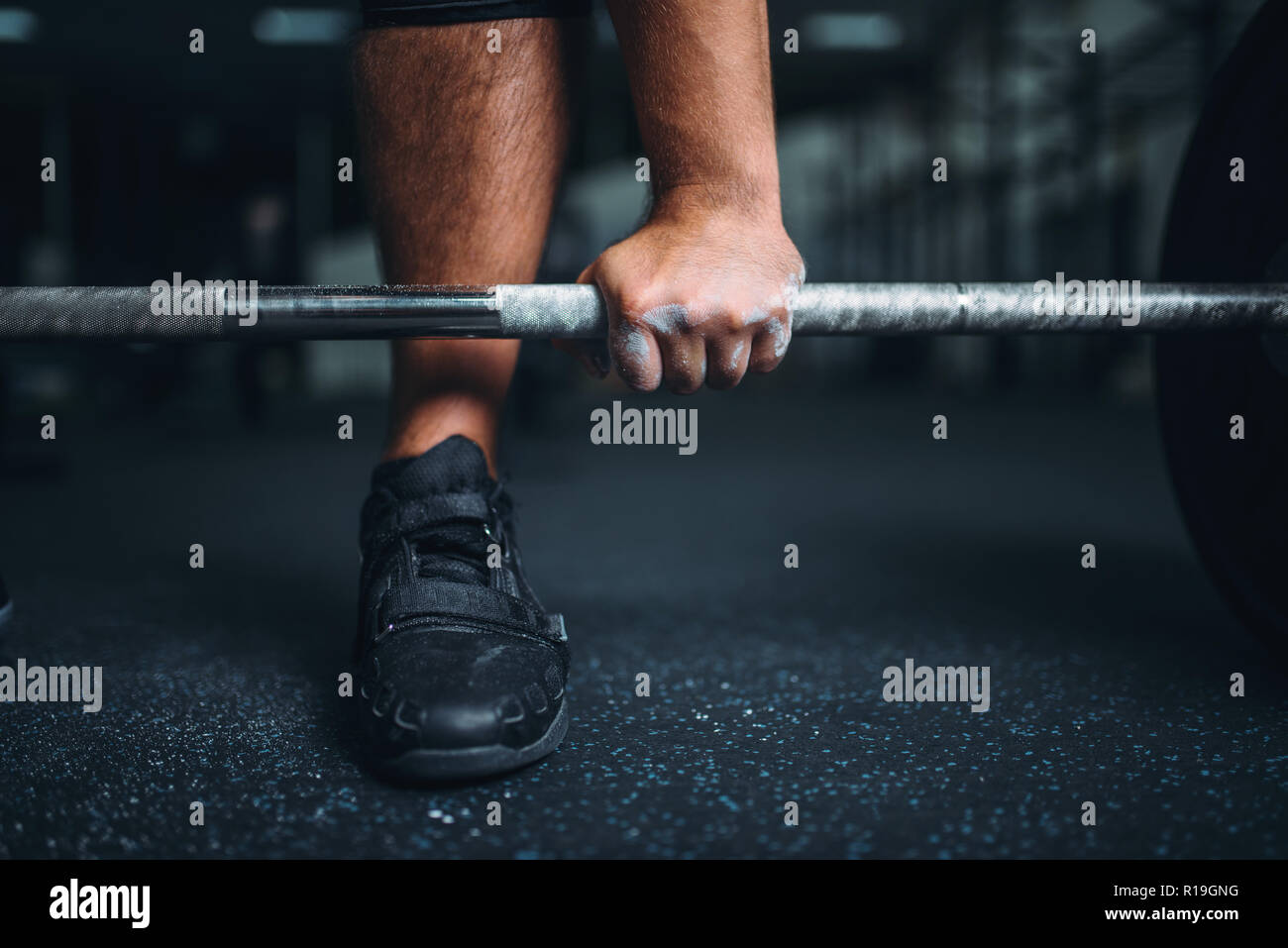 Male powerlifter prepares for deadlift a barbell in gym