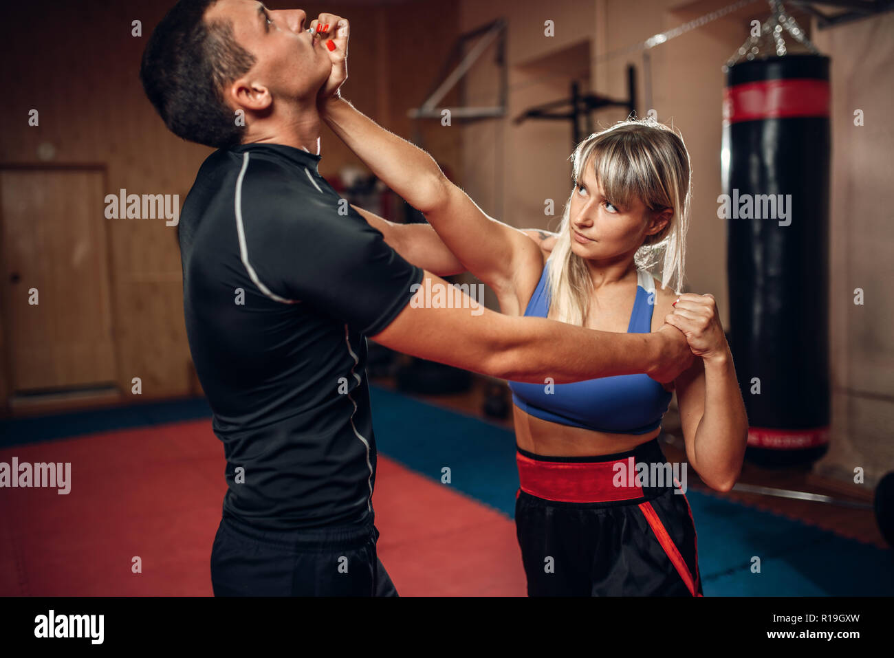 Female person on self-defense workout with male personal