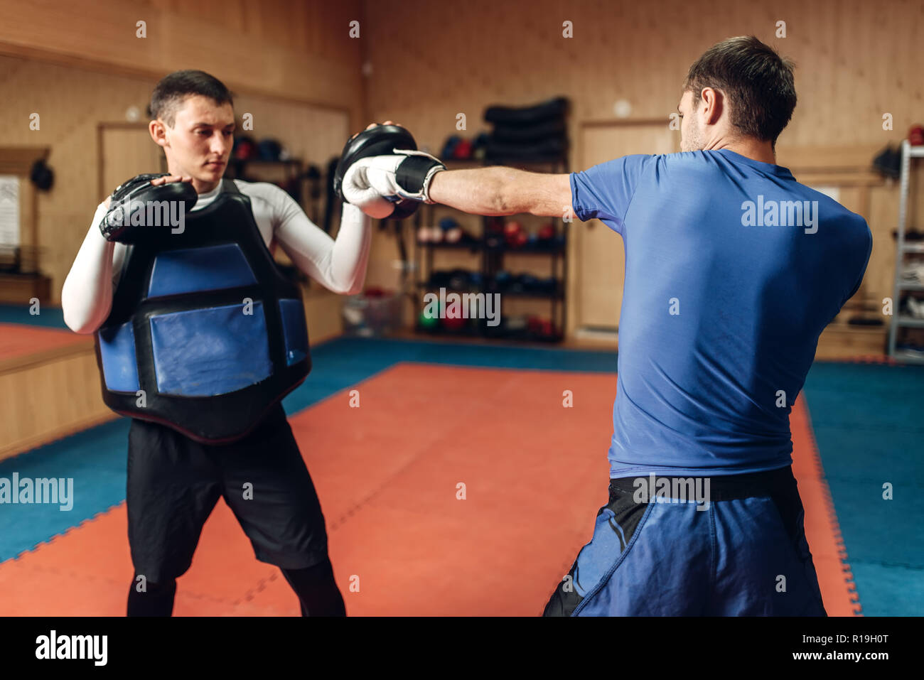 Male kickboxer in gloves practicing hand punch with a personal trainer in pads, workout in gym. Boxer on training, kickboxing practice Stock Photo