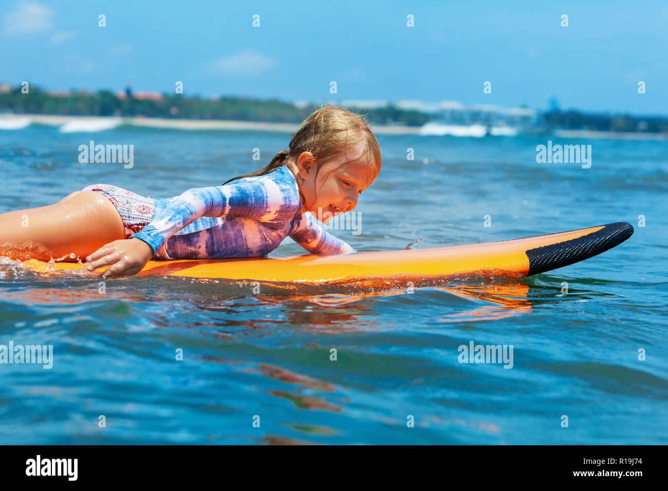 Happy baby girl - young surfer paddle on surfboard with fun on sea waves. Active family lifestyle, kids outdoor water sport lessons, swimming activity - Stock Image