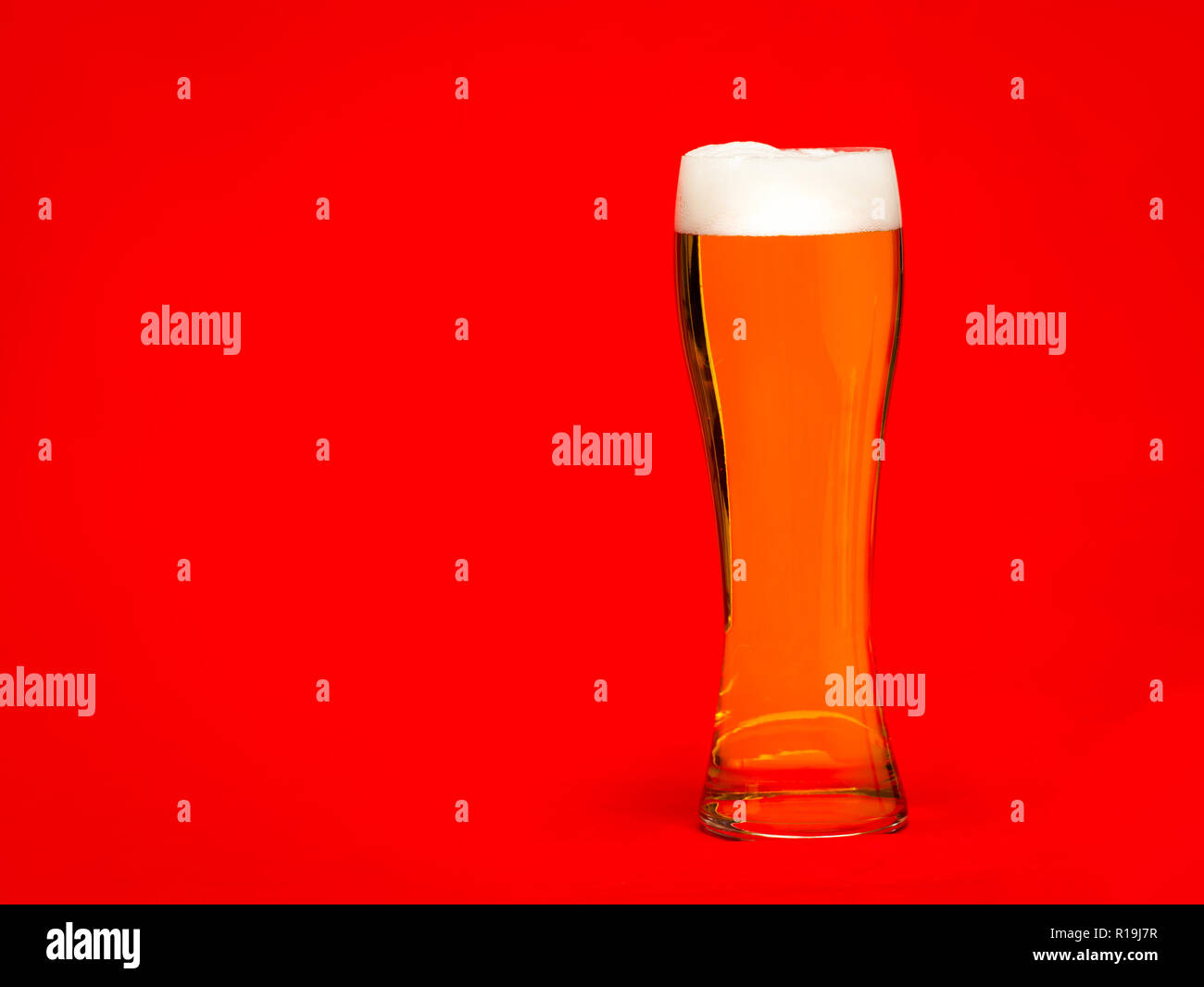 Full pilsner glass of pale lager beer or ale with a head of foam on red background - Stock Image