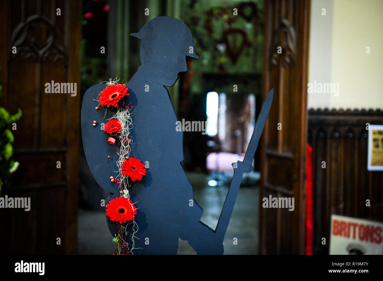 Margam, South Wales, UK. 10th November 2018 Red flowers drape from a silhouette of a soldier at Margam Castle in South Wales, UK, as part of the Lest We Forget floral exhibition which is being held at Margam Country Park, just one of the many remembrance events happing all over the UK to honour those who lived, fought and died in the First World War. Credit: Robert Melen/Alamy Live News - Stock Image