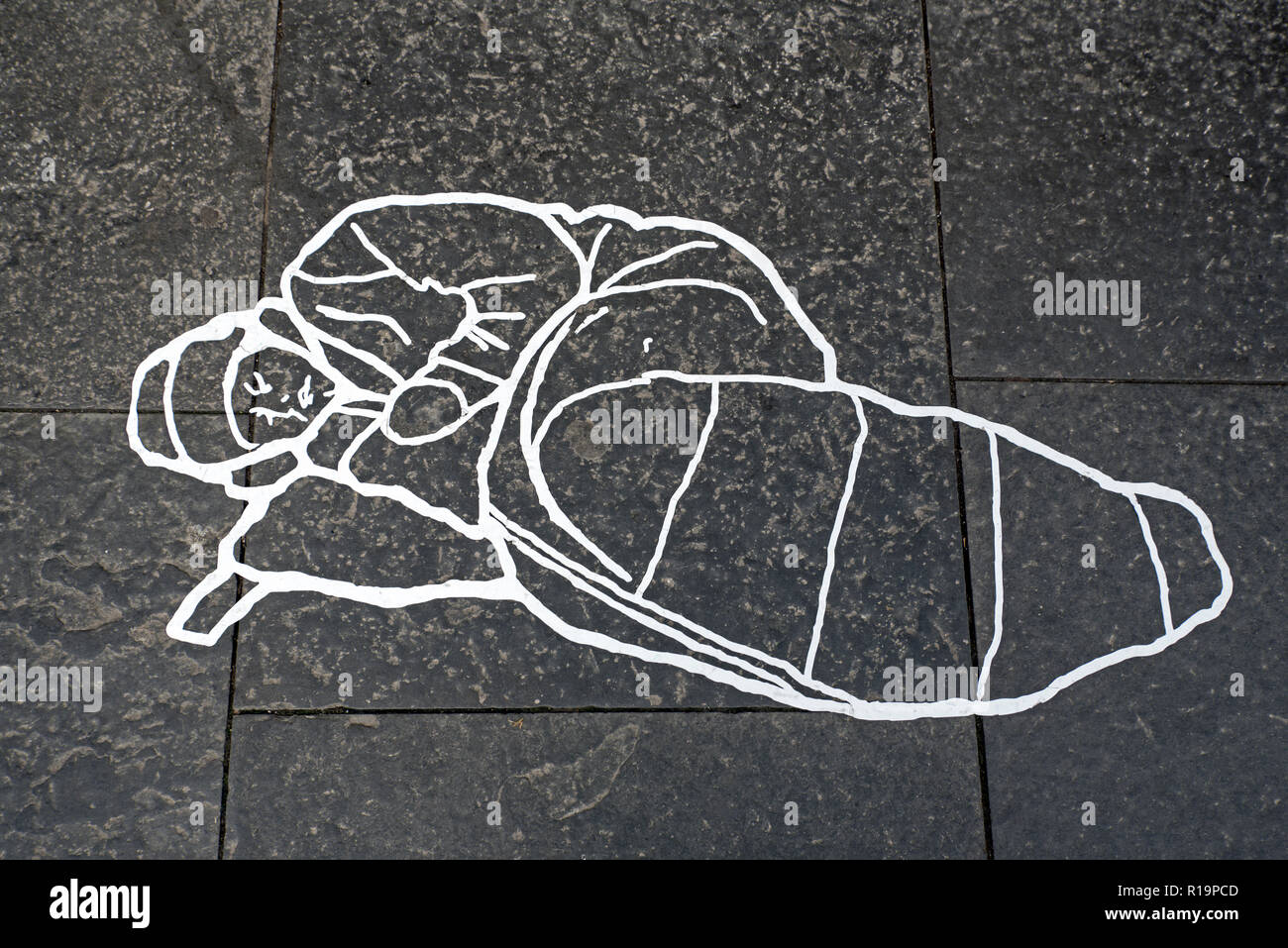 Edinburgh, Royal Mile,  10th November 2018. An anonymous street artist makes a statement about homelessness in the form of a 'reserved' area with line markings in the shape of a homeless person on The Royal Mile, Edinburgh, Scotland, UK. - Stock Image