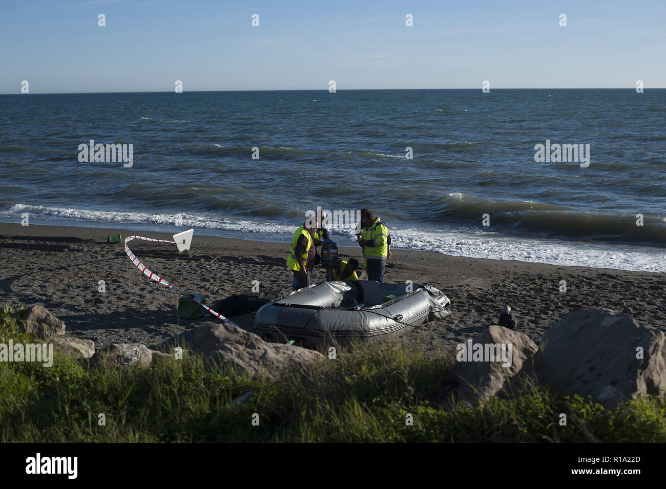 Malaga, MALAGA, Spain. 10th Nov, 2018. Police officers seen inspecting the dinghy after arriving on the beach with a group of migrants.A dinghy with migrants and two dead arrived at the Chilches beach near the coast of Velez Málaga, in Malaga. According to the media and witnesses, some of the migrants from Morocco escaped at the beach while the two corpses were found inside the small boat. Credit: Jesus Merida/SOPA Images/ZUMA Wire/Alamy Live News - Stock Image