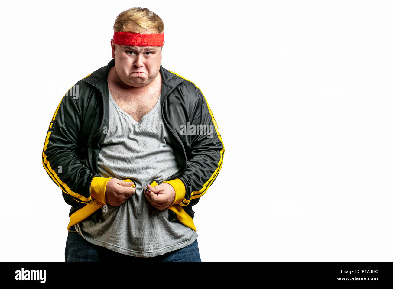 Middle age man with big belly trying to fasten spot jacket - Stock Image