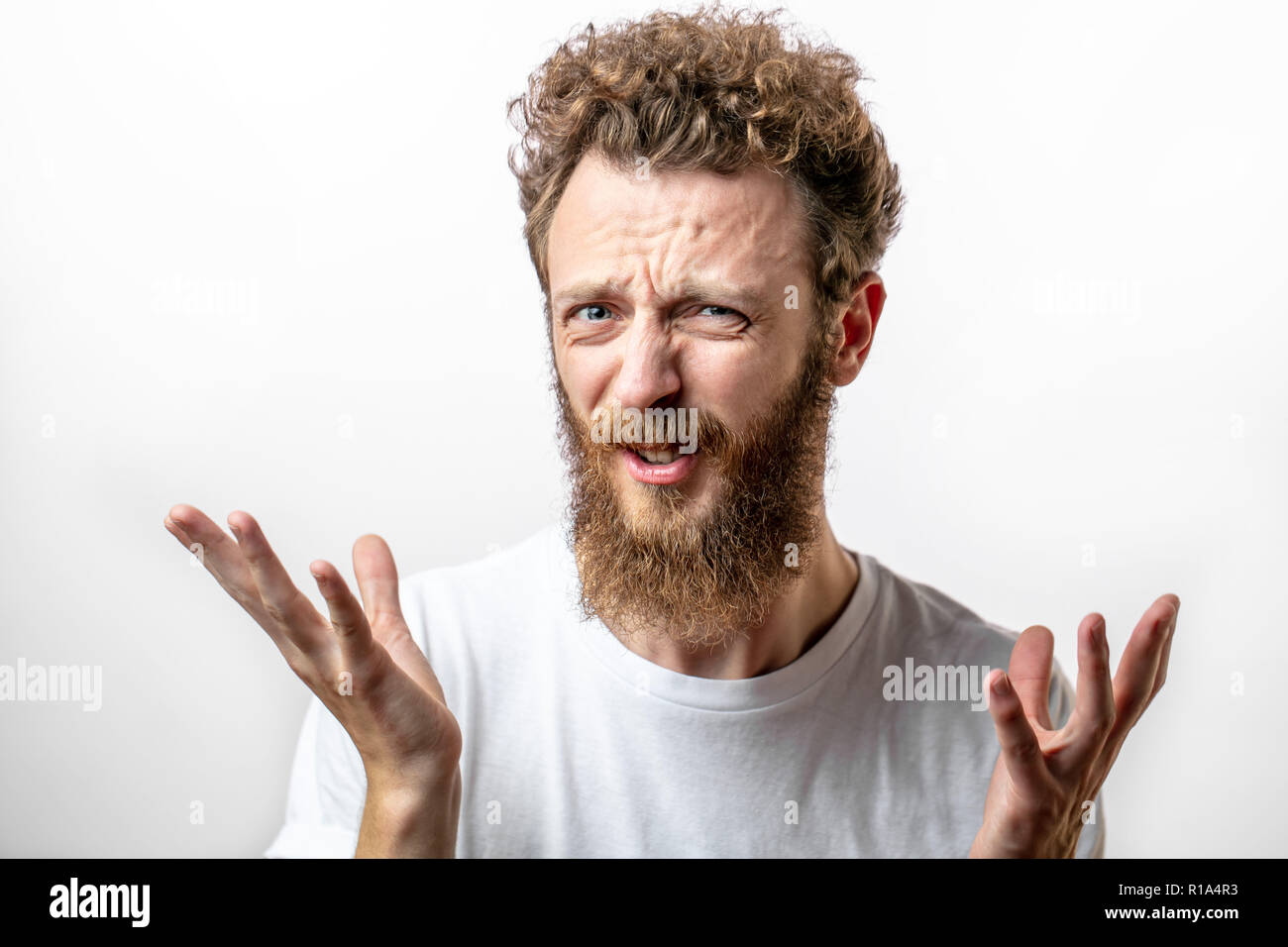 Close up portrait of grumpy young bearded man in t-shirt looking at camera. - Stock Image