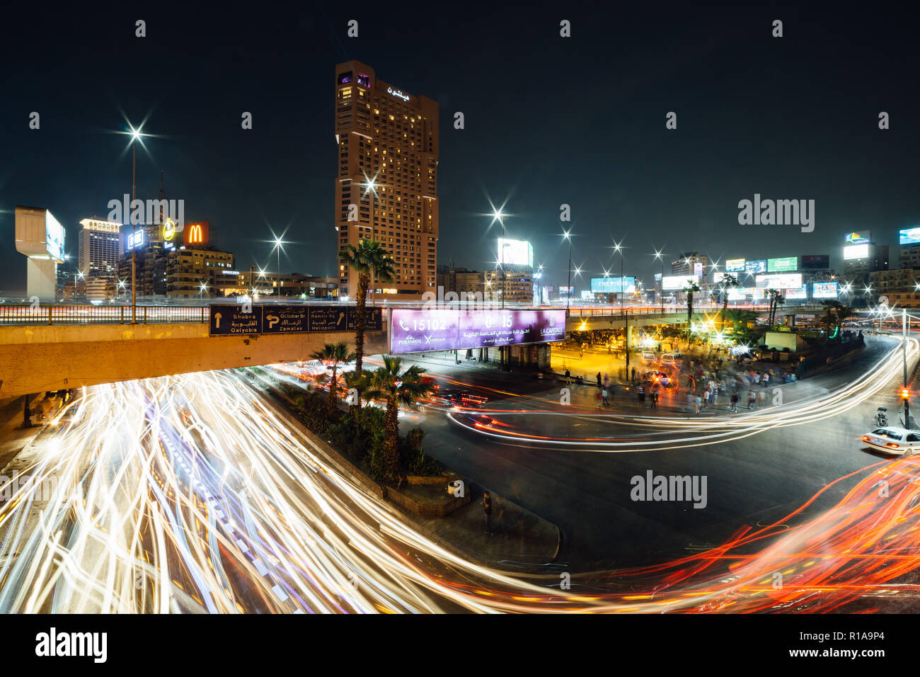 Cairo, Egypt - November 8, 2018: The busy Abdel Munim Riad square and bus station in central Cairo at night, long exposure with traffic light trails. - Stock Image