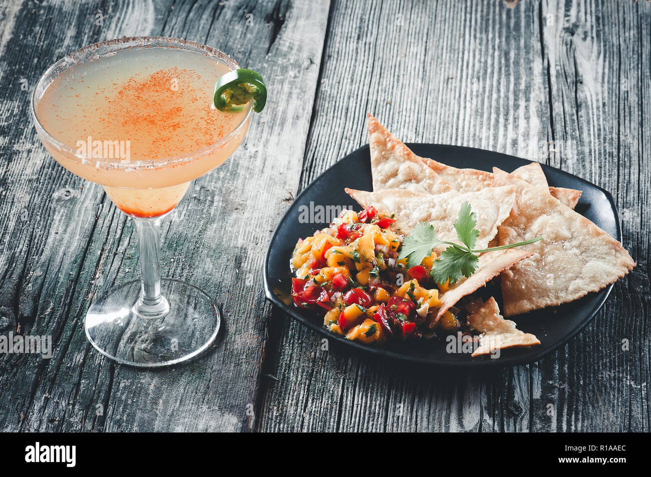 Spicy margarita with fresh mango salsa and home made tortilla chips. - Stock Image
