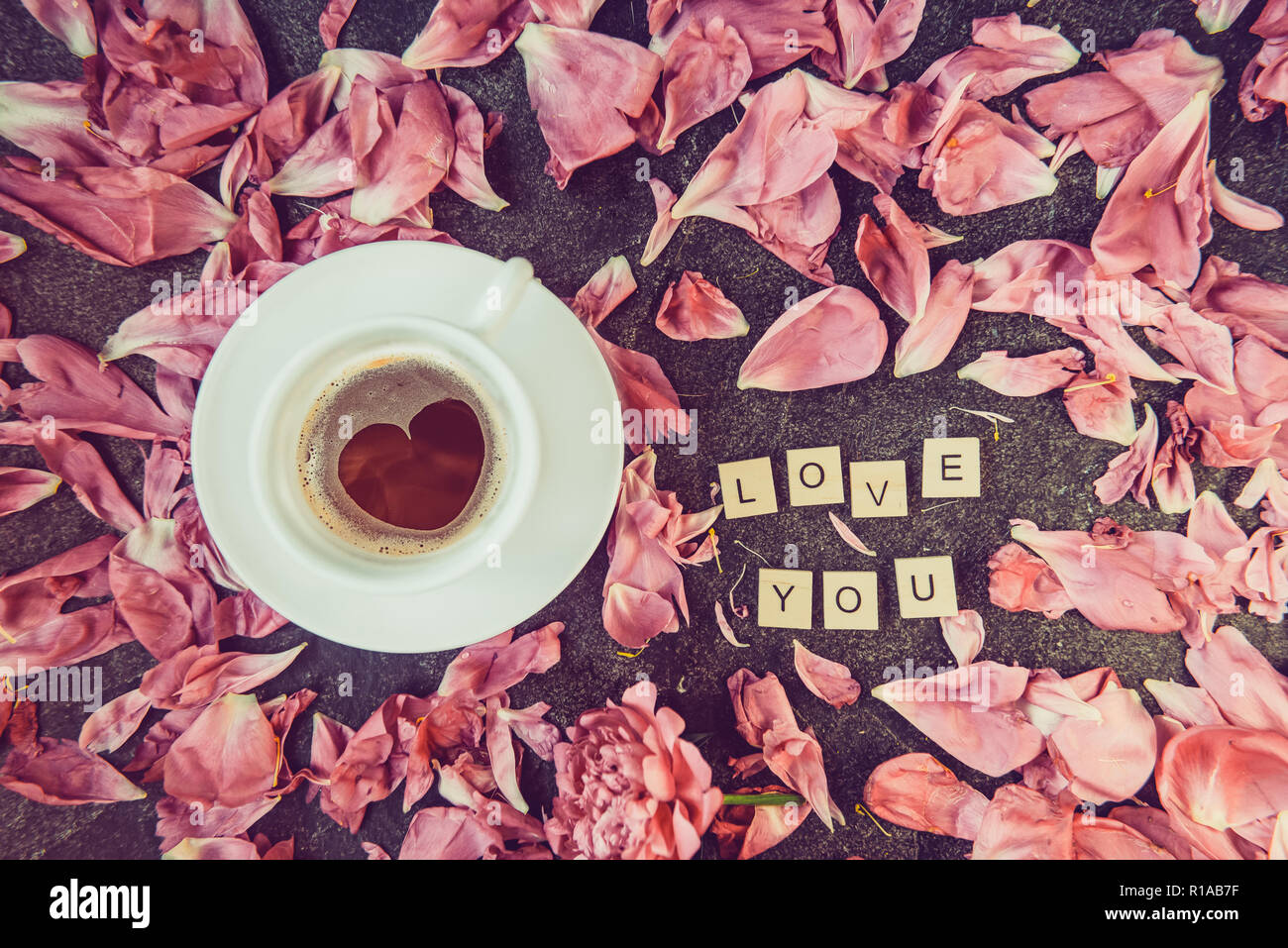 Flatlay cup of coffee with heart shape pattern and message I love you spelled in wooden blocks with pink peony flower petals on dark background. Valen Stock Photo