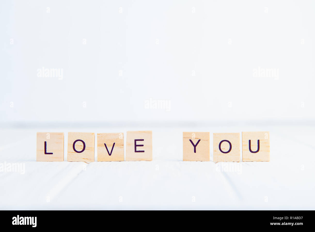 Message I love you spelled in wooden blocks standing on white wooden table. Valentines day background. Simplicity concept. Selective focus. Copy space Stock Photo