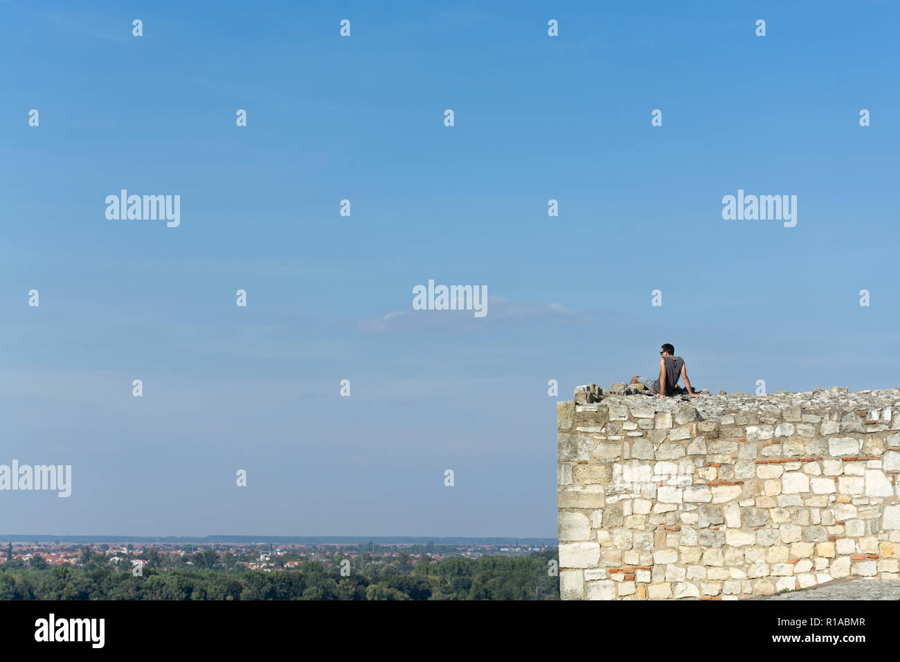 Dark haired young man with sunglasses and ear pods overseeing the cityscape on a bright summer day from the stone watchtower of Kalemegdan fort in Bel - Stock Image