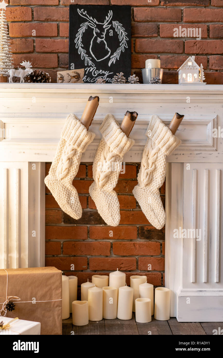 White wool socks for Santa on the fireplace. Loft apartments, brick wall with candles and Christmas tree wreath. - Stock Image