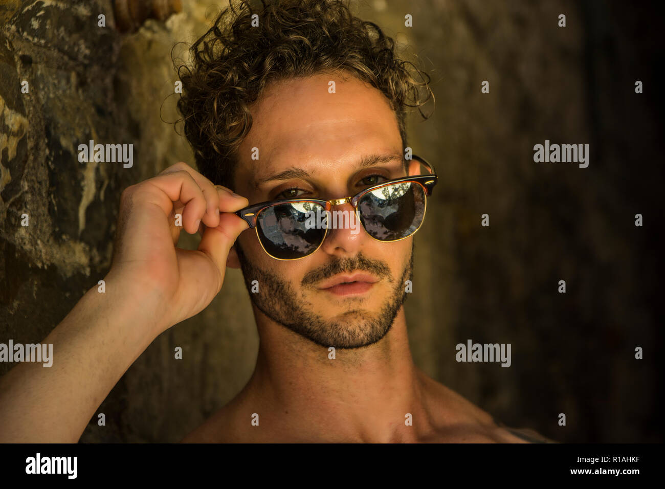 Headshot of handsome unshaved man wearing sunglasses outdoor in old town - Stock Image