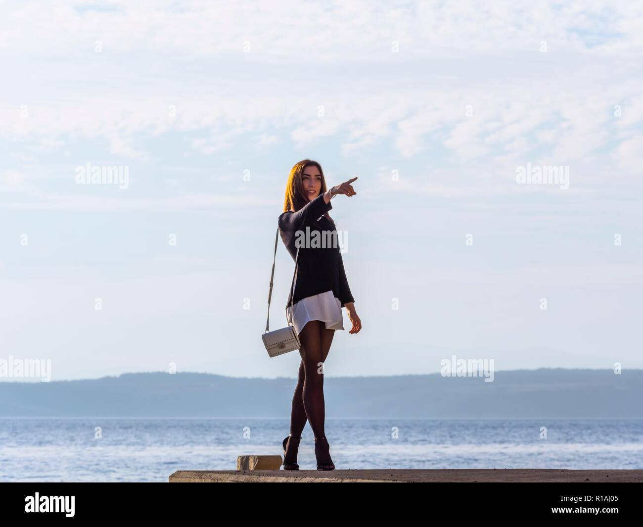 Walking teen girl outside full length pointing showing something in distance with extended finger hand panty-hose legware legwear leggings Stock Photo