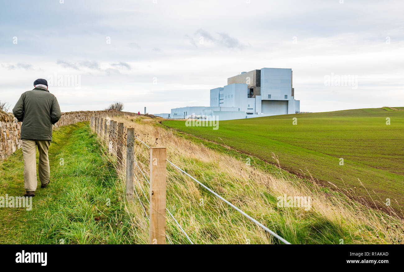 Older man walking on coastal path by Torness nuclear power station, East Lothian, Scotland, UK - Stock Image