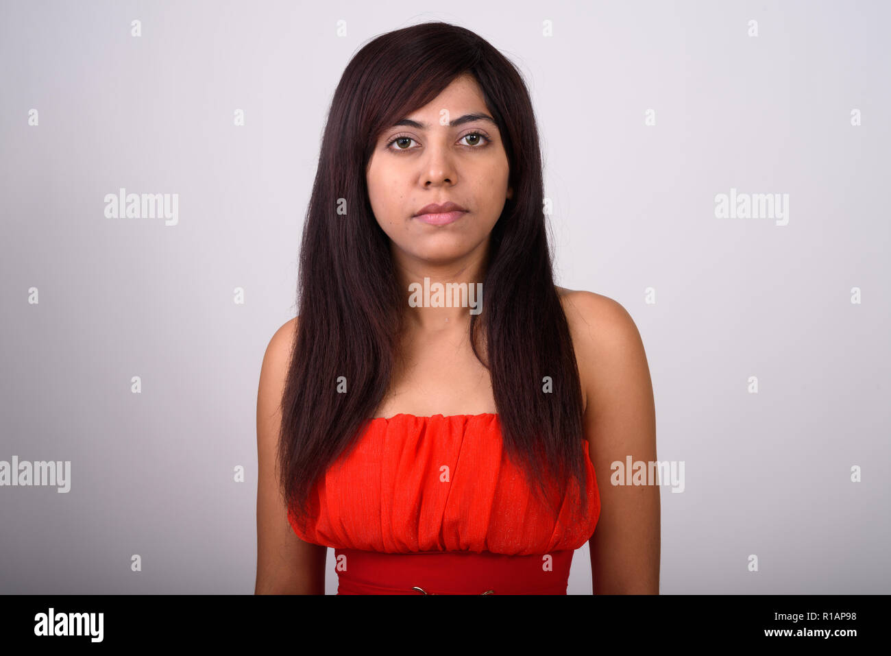 2887df027f Close up of young Persian woman wearing red dress against gray b ...