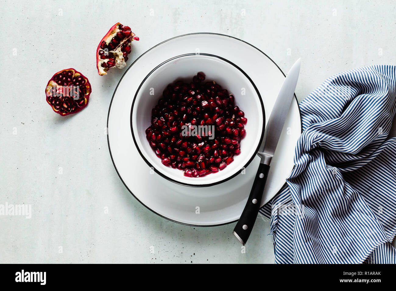 pomegranate seeds in white enamel bowls on the table napkin and