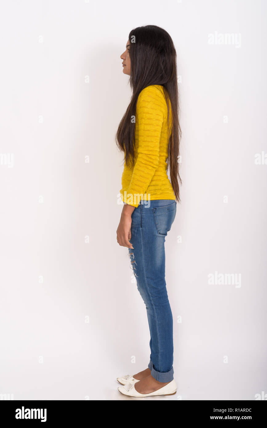 Full body shot profile view of young Indian woman standing again Stock Photo