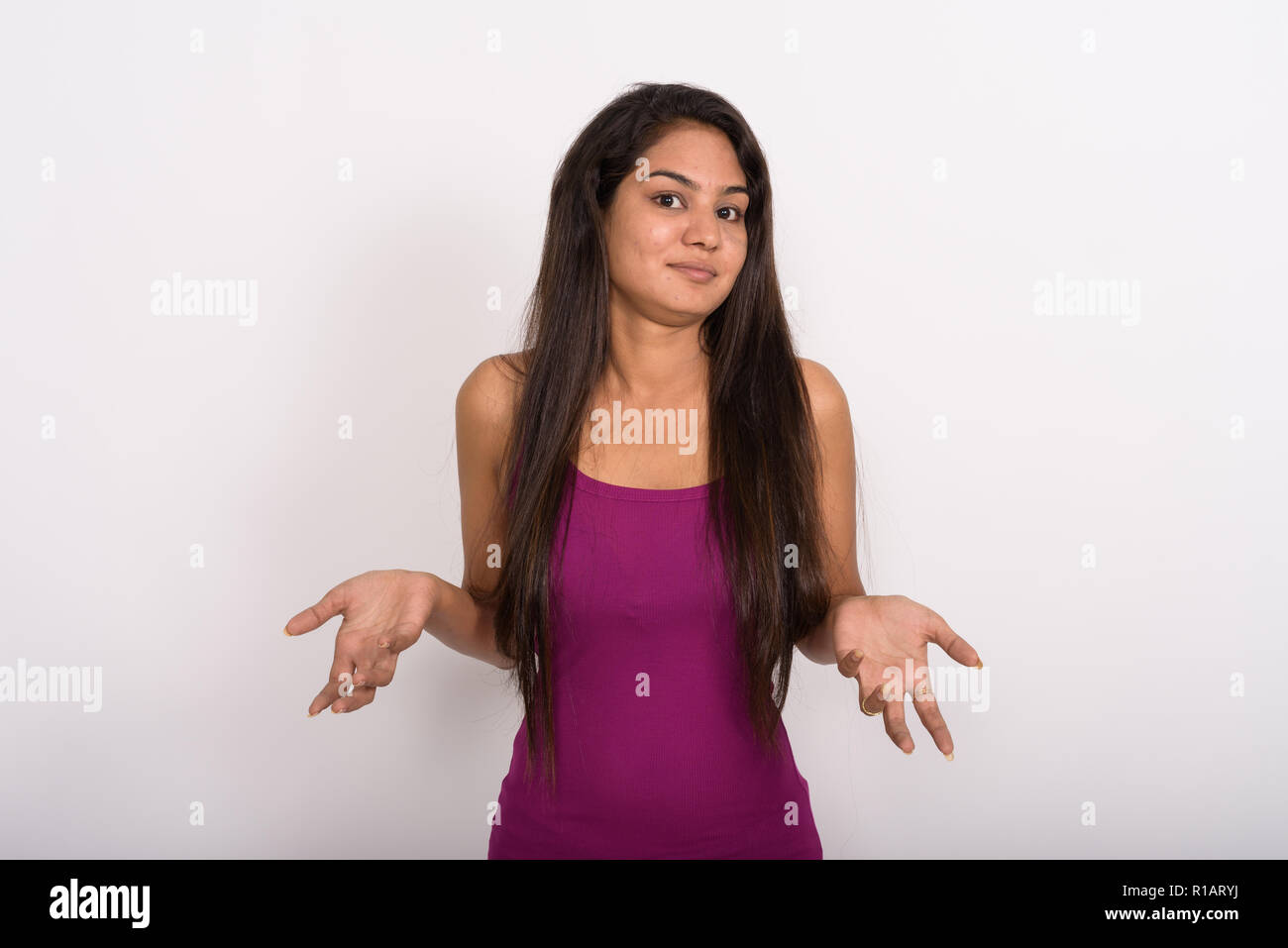 Studio shot of young Indian woman looking confused against white - Stock Image