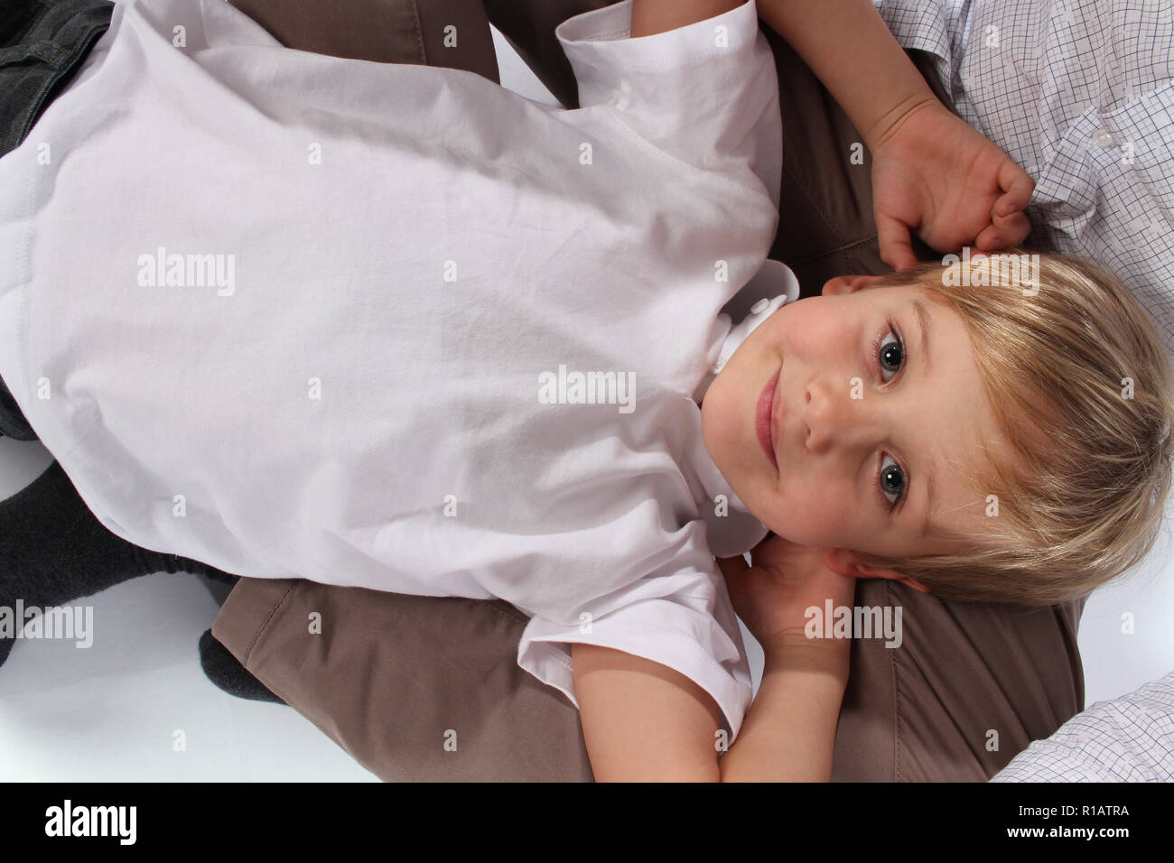 Adorable cute little boy lying in his daddy's lap - Stock Image