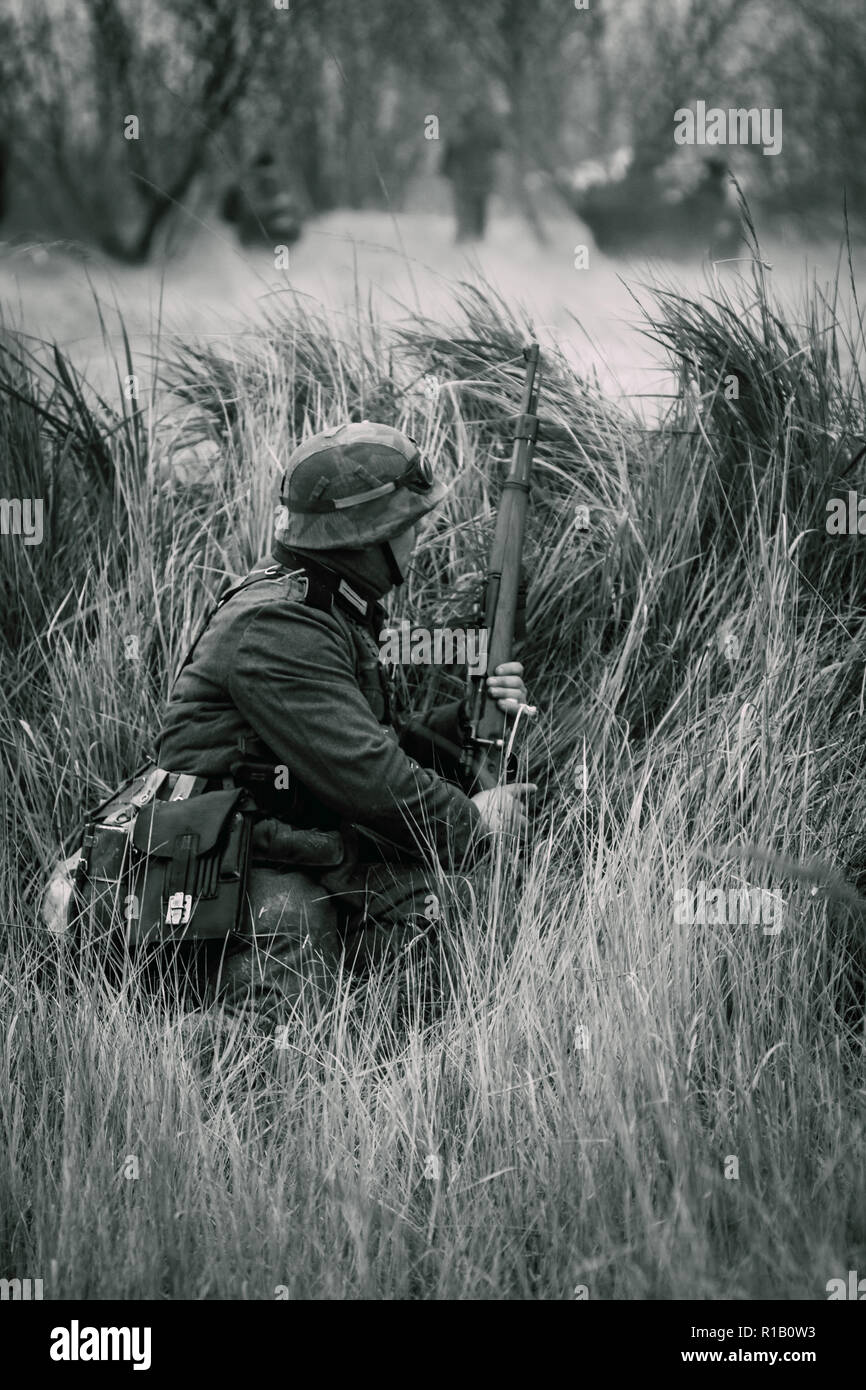 Wehrmacht soldier World War II in ambush in the tall grass with a rifle and full uniform. Black and white shot Stock Photo