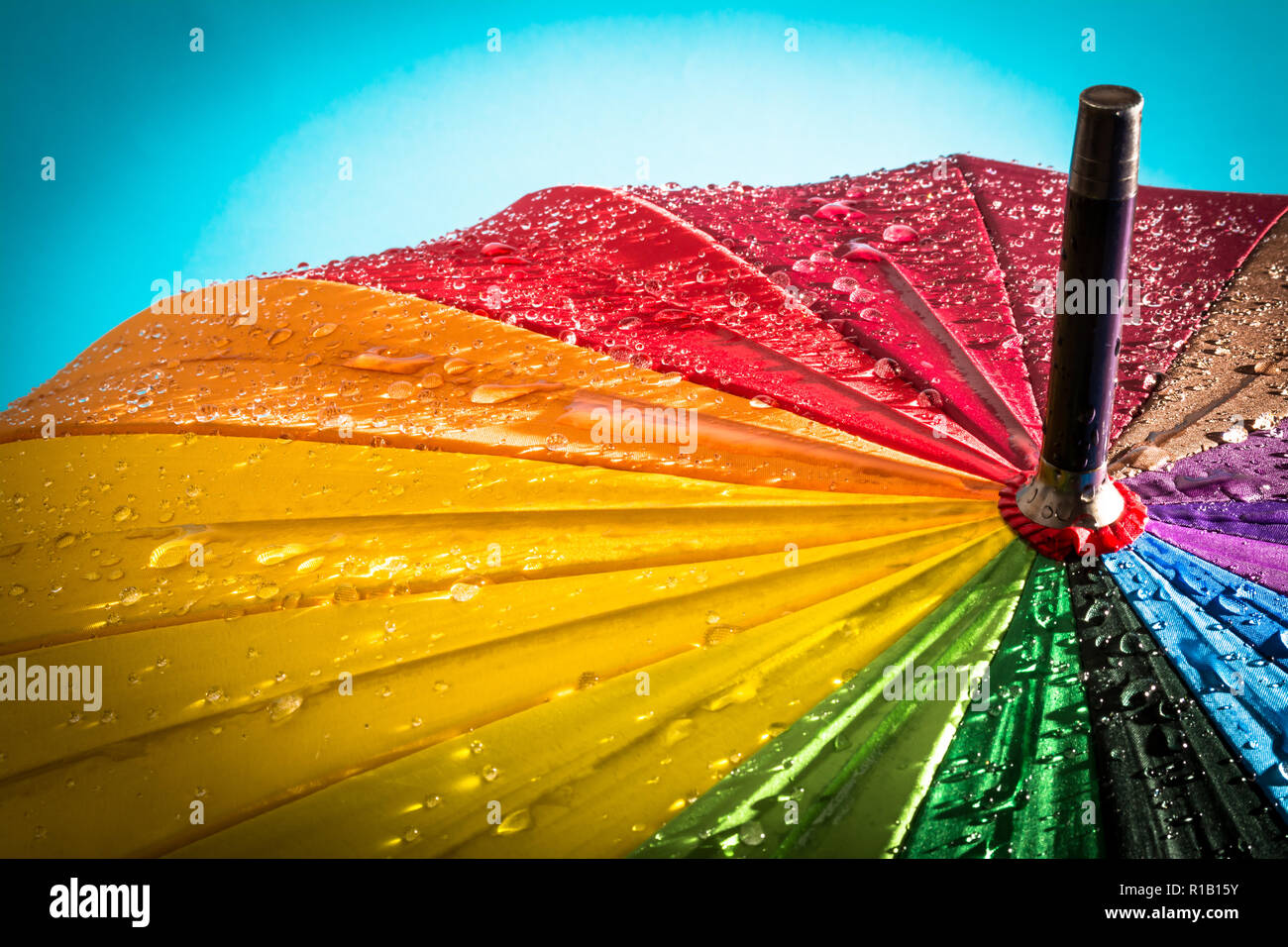 Multi-colored colorful umbrella with all colors of the rainbow with raindrops. Stock Photo