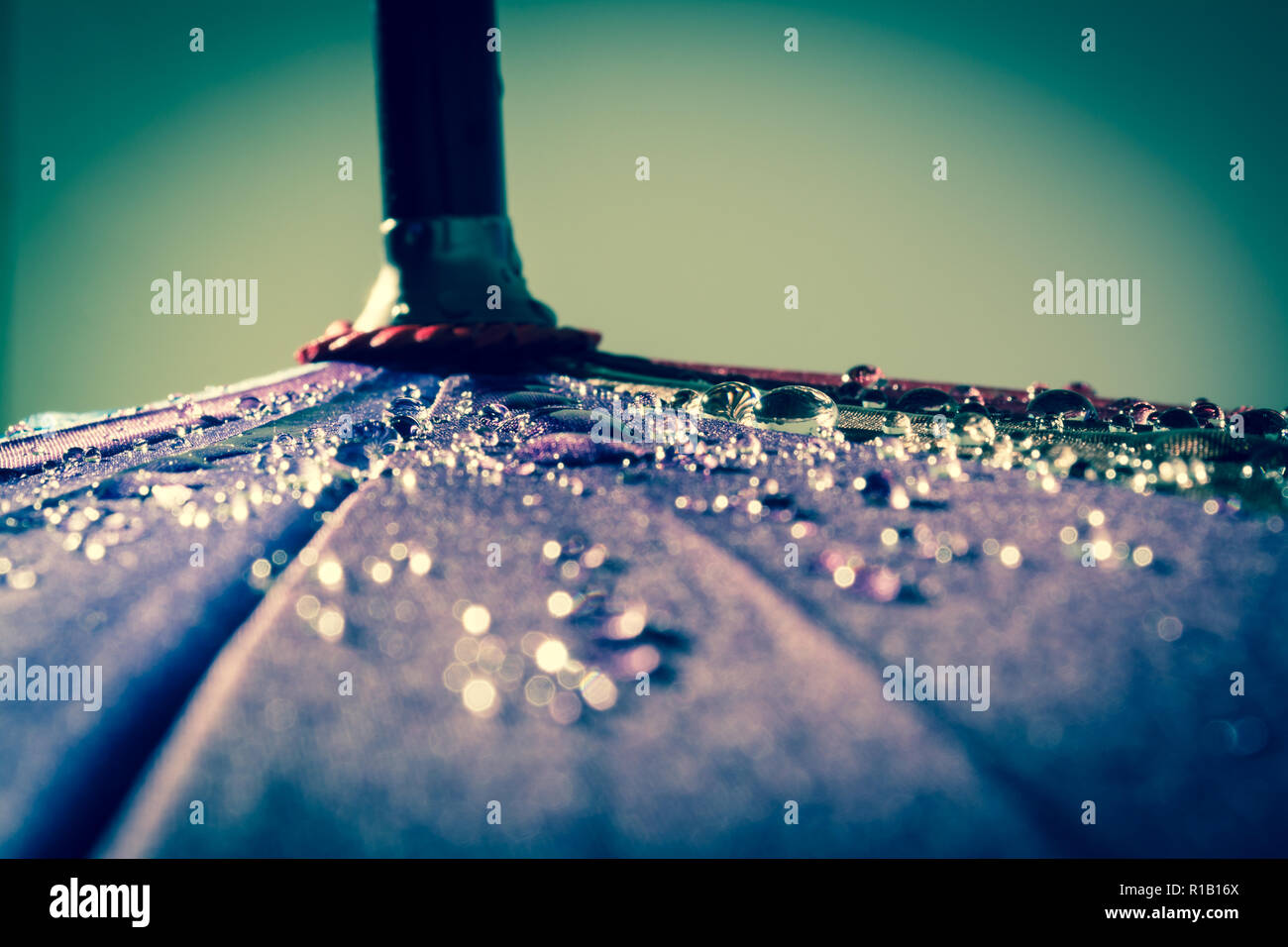 Raindrops on a colorful umbrella with all the colors of the rainbow close-up macro waterdrops background. Vintage, grunge, old, retro style photo. Stock Photo