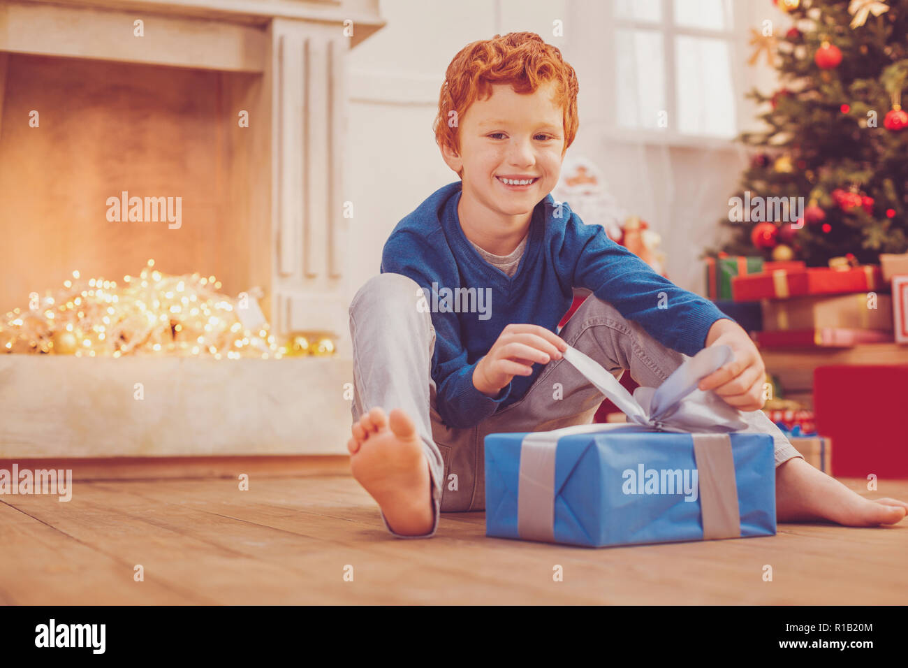 Cheerful preteen boy opening his Christmas present - Stock Image