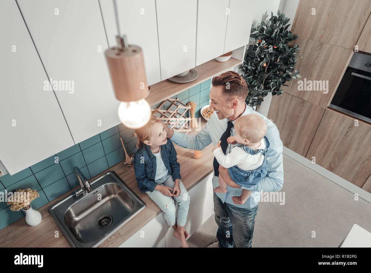 Satisfied lovely father smiling and spending time with children. - Stock Image