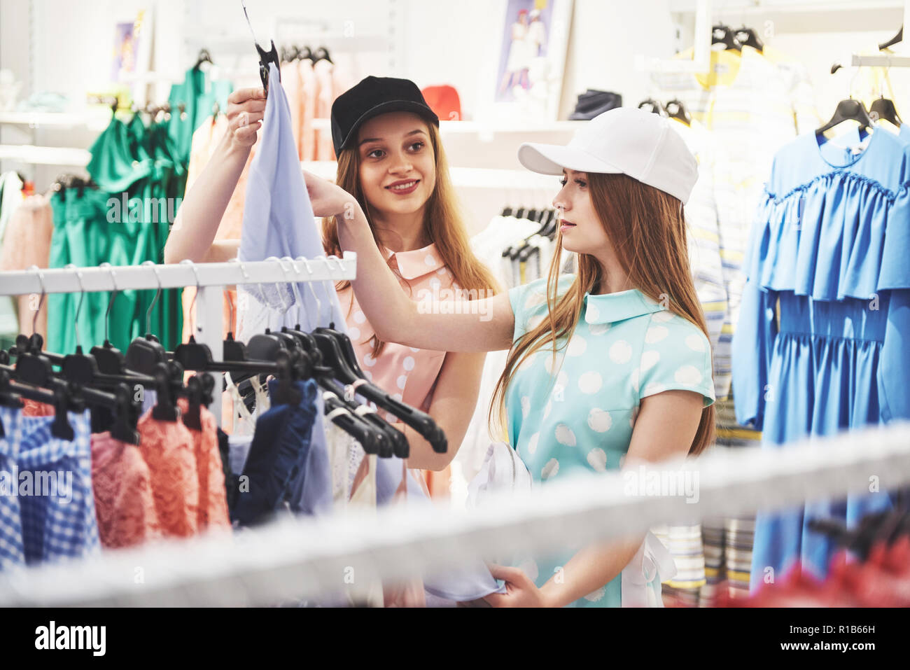 Shopping therapy in action. Rear view of two beautiful women with shopping bags looking at each other with smile while walking at the clothing store - Stock Image