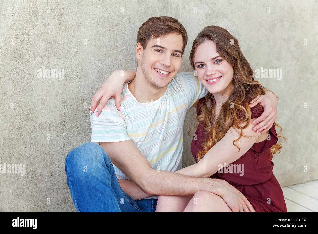 Couple in love having nice time together. Young happy woman hugging boyfriend, white background. Students, bride, groom, engagement, relationship, asp - Stock Image