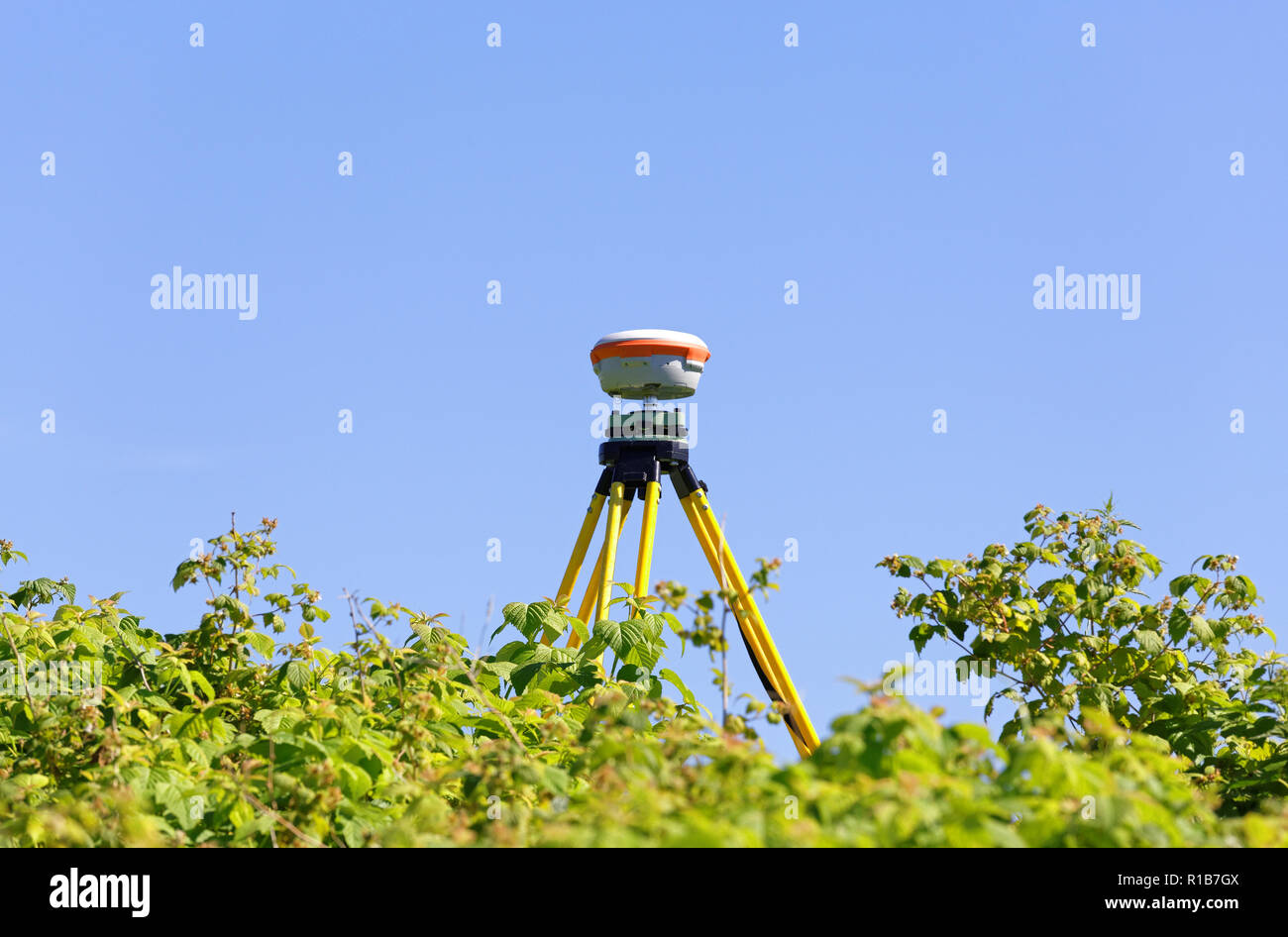 GNSS-geodetic receiver mounted on an old tripod against the background of blue sky and foliage of wild raspberry bushes. Practical application in the  - Stock Image