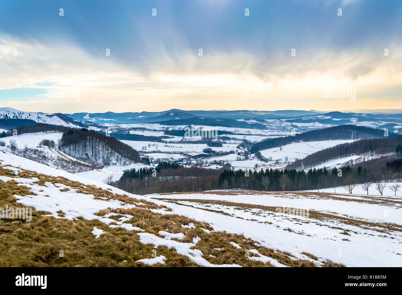 Winter landscape on Wasserkuppe with snow and dramatic sky in Rhoen Mountains, Germany - Stock Image
