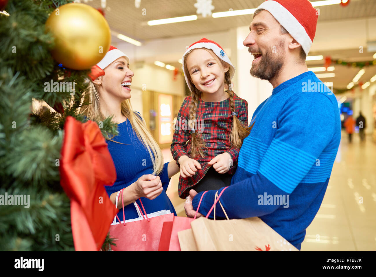 3ffd3f76a Laughing family in Santa hats standing in mall Stock Photo ...