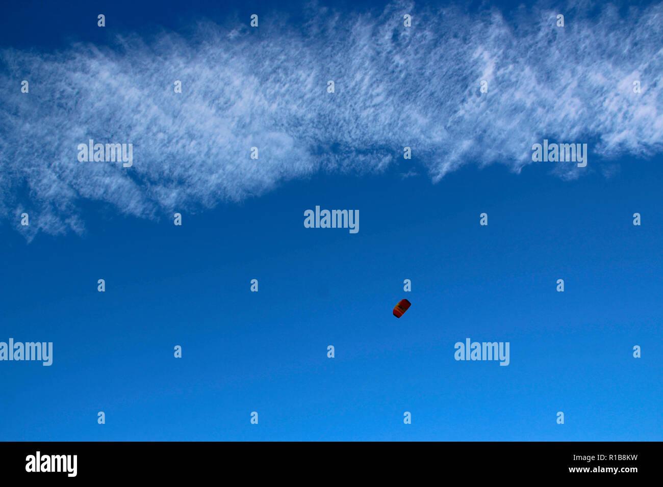 Lenkdrachen am blauen Himmel mit einigen Wolken. Fly a kite n a blue sky with a few nice clouds. - Stock Image