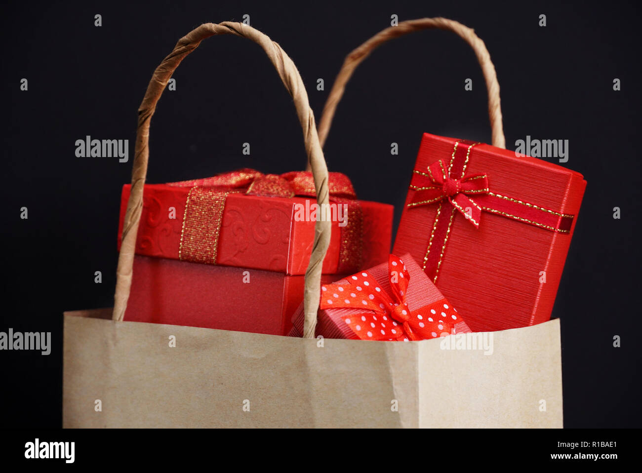 8b62c43c112c Tree red gift box in shopping bag on black background for shopping theme. -  Stock