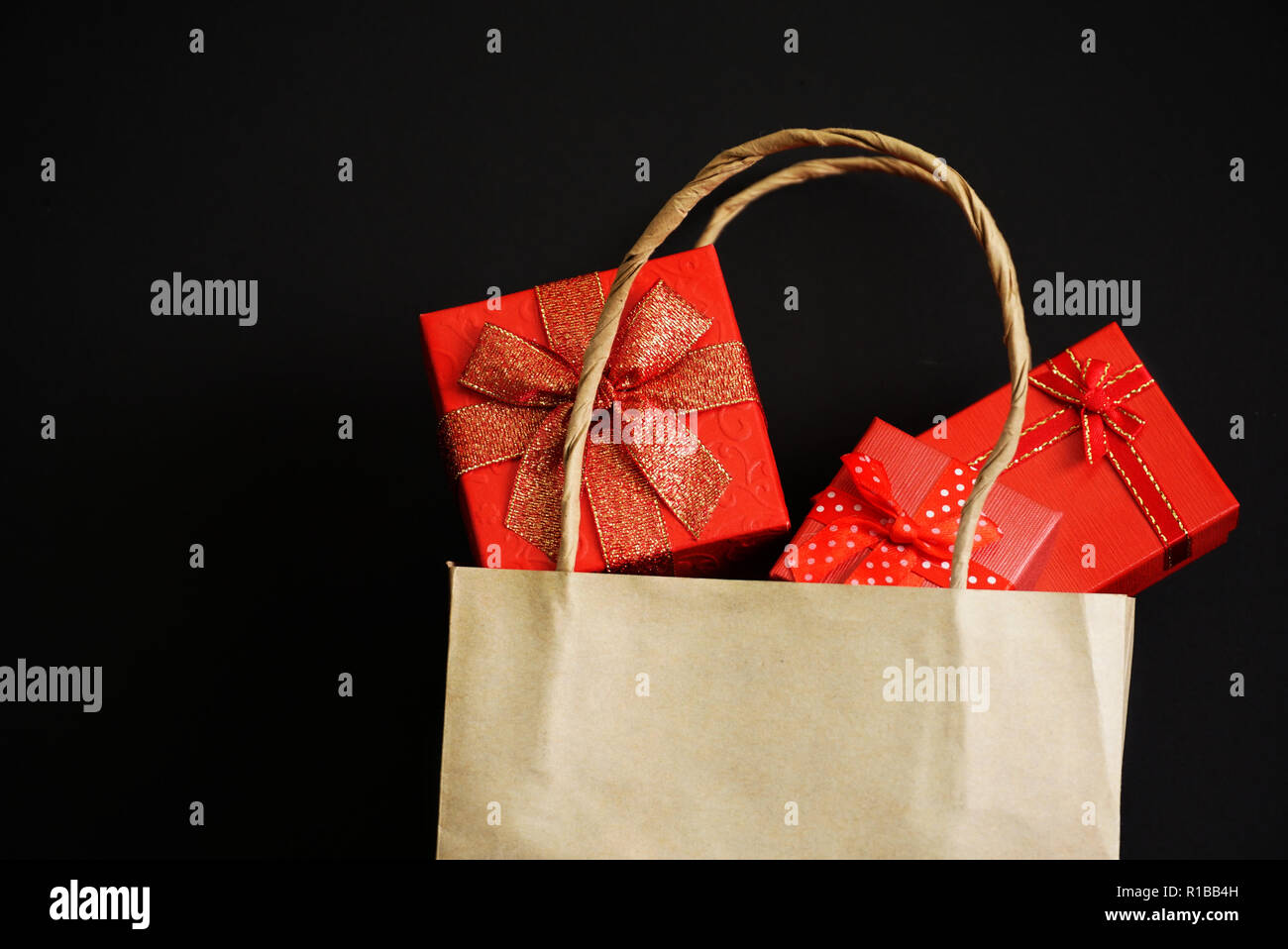 Tree red gift box in shopping bag on black background for shopping theme. - Stock Image